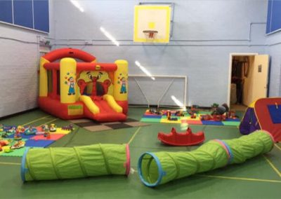 Sports hall set up for childs play with an inflatable and toys