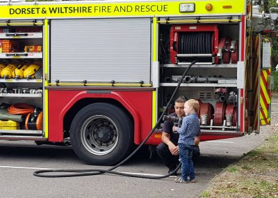 A young boy learns about fire fighting using a big hose